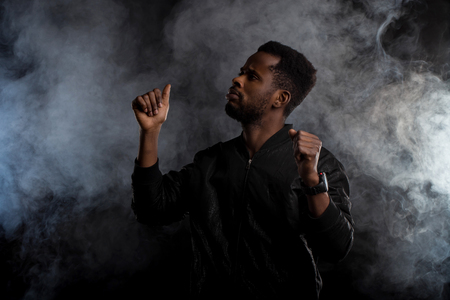 Photo pour Waist up shot of handsome confident young african american man in black jacket with beard gesturing as dancing, raising hands up, looking to side seriously against white smoke on dark background. - image libre de droit