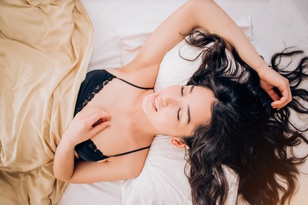 Photo pour From above sexy beautiful brunette girl with long wavy hair lying on white bed in sensual clothes. She touching body, looks enjoyed with closed eyes, dreaming, relaxing. Good dream, underwear concept. - image libre de droit