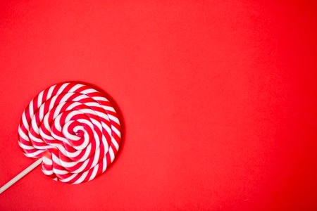 Photo for Sweet round red and white lollipop. Colorful striped lollipop on coral background with copy space. Top view. Valentine's day, children's holiday, sweets, candy concept. - Royalty Free Image