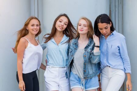 Photo pour group of female students in summer clothes posing together outdoor and looking at camera. Fashion portrait of young student girlfriends - image libre de droit