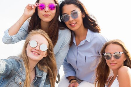 Photo for Close up portrait of four beautiful young student girl in colorful sunglasses on the background of the sky - Royalty Free Image