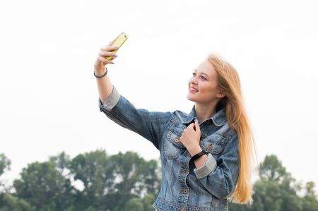 Photo for Beautiful blonde woman with long hair and in jeans with a smile makes a selfie on the background of nature and the sky - Royalty Free Image