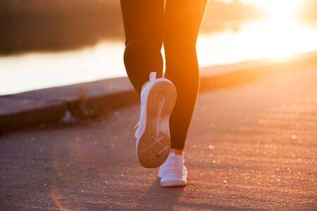 Foto de Closeup white sneaker of athlete woman runner feet on sunset background - Imagen libre de derechos
