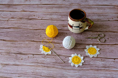Photo pour Crocheted daisy, balls of colored yarn, scissors, and a cup of coffee on wooden background - image libre de droit