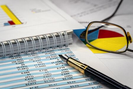 Foto de Accounting business concept. Glasses and pen with accounting report and financial statement on desk. - Imagen libre de derechos