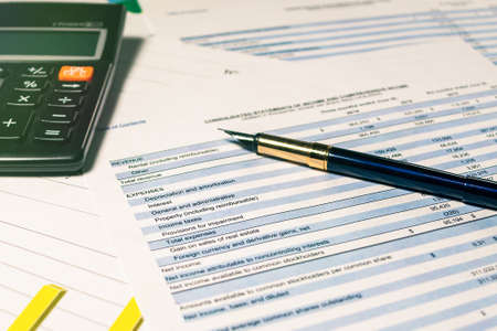 Photo pour Calculator and pen with accounting report and financial statement on desk. Accounting business plan concept. Selective focus - image libre de droit