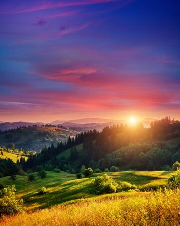 Photo pour Beautiful green hills glowing by warm sunlight at twilight. Dramatic scene. Colorful sky, red clouds. Carpathian, Ukraine, Europe. Beauty world. - image libre de droit