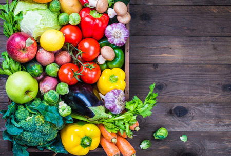 Vegetables and fruits on rustic wood background copy space.