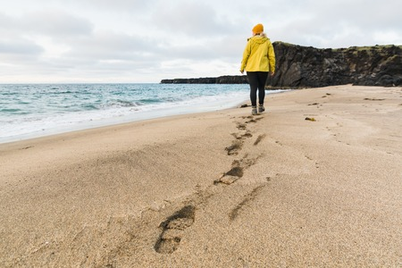 Photo pour Girl in yellow raincoat walking on the sand of Skardsvik beach at sunset. Focus on footprints, wide angle lens shot, Snaefellsnes peninsula, Iceland. - image libre de droit