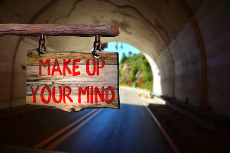 Make up your mind motivational phrase sign on old wood with blurred background