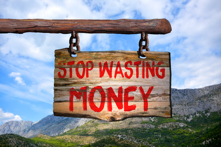 Stop wasting money motivational phrase sign on old wood with blurred background