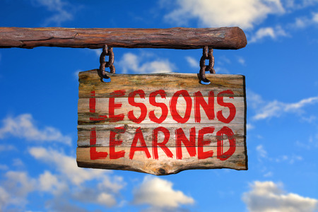 Lessons learned motivational phrase sign on old wood with blurred background