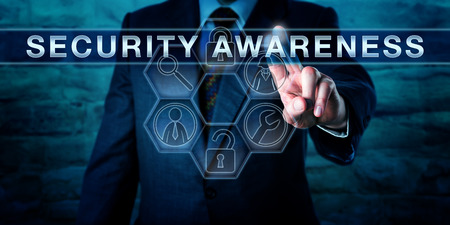 Foto de Industry consultant is pressing SECURITY AWARENESS on an interactive touch screen interface. Information technology concept for both computer or cyber security and physical asset protection. - Imagen libre de derechos