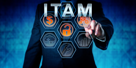 Business person is touching ITAM on an interactive virtual control monitor. Business strategic metaphor, information technology concept, corporate terminology and acronym for IT Asset Management.