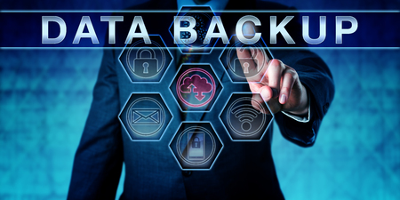 Photo pour Business manager pushing DATA BACKUP on an interactive virtual control screen interface. Information technology concept for copying files or databases for future use in data recovery upon data loss. - image libre de droit