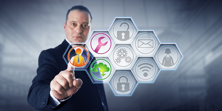 Photo pour Confident business director is activating three managed services icons by touch on a control screen. The remaining six of nine IT buttons remain gray. Concept for efficiency through managed services. - image libre de droit