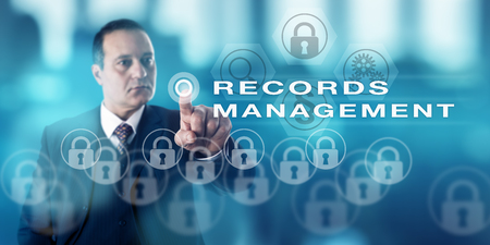 Photo pour Information technology director with serious look is pressing a push button to call RECORDS MANAGEMENT. Content management metaphor and business administration concept for public and private sector. - image libre de droit