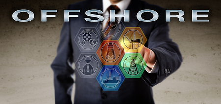 Corporate manager in blue business suit activating OFFSHORE on an interactive virtual remote control screen. Oil and gas industry technology concept for exploration and drilling below the seabed.