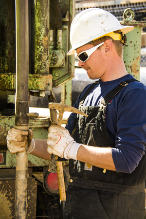 A Leppert Associates drilling hand working on a bit for a Drill Rig