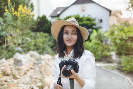 Photo pour Young asian woman in white shirt and hat in a park, smiling, holding camera. Outdoor portrait. - image libre de droit