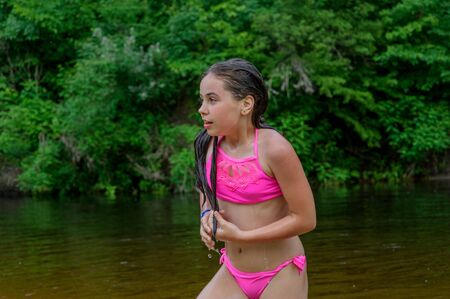 Foto de little brunette girl in pink bathing suit sitting in the sand. Little girl in a bathing suit by the river. Summer outdoor recreation by the river. Relax. girl 9 years old resting in the summer. - Imagen libre de derechos