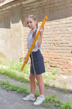 Photo pour Elementary schoolgirl standing by school gate. Beautiful brunette schoolgirl in school uniform with a yellow ruler. Girl 10 years old with two pigtails and stylish hair color. Life style. School. - image libre de droit
