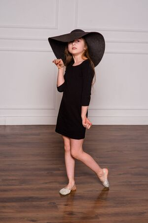 Photo for little fashion model in dress photo in photostudio backstage. A child of a girl of 8-9 years old is posing as an adult. Long hair. Modern children. Schoolgirl on a photo shoot. - Royalty Free Image