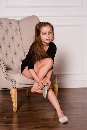 Photo pour little fashion model in dress photo in photostudio backstage. A child of a girl of 8-9 years old is posing as an adult. Long hair. Modern children. Schoolgirl on a photo shoot. - image libre de droit