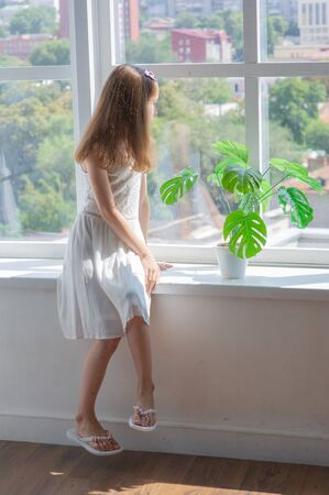 Photo pour Little girl in white dress.Little girl in a white dress by the window.Little girl at the window with a city view.Pensive girl. Brown hair at the girl.Lace white dress for a girl of 9-10 years old - image libre de droit