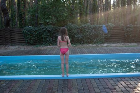 Photo pour Cute baby have fun on vacation. Children bathe in pool. Little child enjoying pool indoors. girl bathes in the pool. Pool in the forest. Rest in the woods of a child with his family.Girl 9 years old - image libre de droit