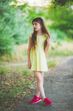 Photo pour Girl walks in the woods. Girl walking in the park.A little girl of 9 years went for a walk on the street in summer or early autumn. Schoolgirl walking after school. Girl with long hair in a dress - image libre de droit