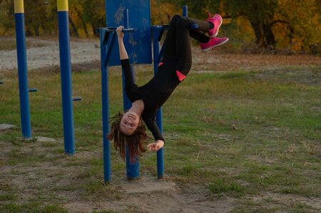 Foto de The girl goes in for sports on the Playground on the street. exercises, stretching, exercises. Healthy lifestyle. Fitness training. Workout. Girl goes in for sports on the playground. Girl likes sport - Imagen libre de derechos
