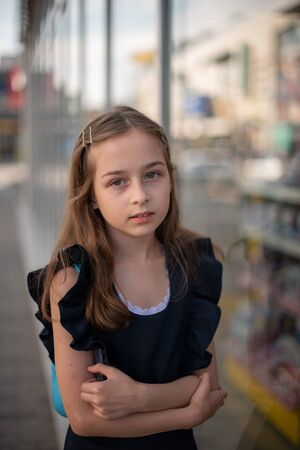 Photo pour Schoolgirl in a blue dress posing on the street. A girl with blond hair 9-19 years old. Soon to school. Girl in a school dark blue dress. Beautiful young girl in vintage dress posing outdoors - image libre de droit