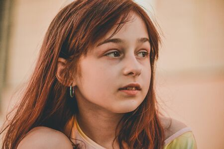 Photo pour Teen girl 9 or 10 years old on the street. Girl on a walk on the street in a t-shirt. Girl with a caret and brown hair. A look to the side. holidays - image libre de droit