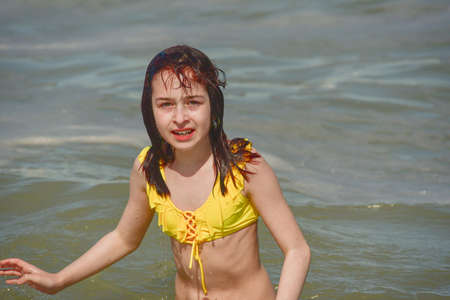 Photo pour Girl at sea. The portrait of the young girl. Teenager summer vacation sand. Sunny day and the sea. Childhood travel vacation. Teenager in a yellow swimsuit on the beach. Teenager swims in the sea - image libre de droit