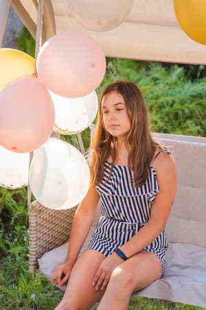 Photo pour Teenager girl and balloons. Girl, balloons, holiday, birthday. Happy moments in life. Girl 11-13 years old. Summer vacation, swing, beautiful brunette. Teenager girl in striped overalls. A party - image libre de droit