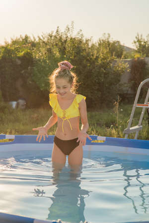 Foto de Joyful childhood. Relaxation concept. Relax by the pool, smile, teenager. A girl in a swimsuit in a frame pool is resting. - Imagen libre de derechos