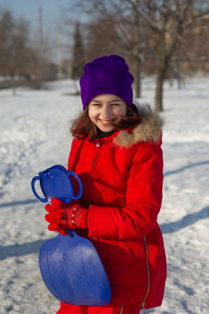 Photo pour Little toddler girl in beautiful warm red outfit playing outdoors in the snow. Girl in a red jacket on the street in winter. A school age girl 9 or 10 years old in winter. - image libre de droit