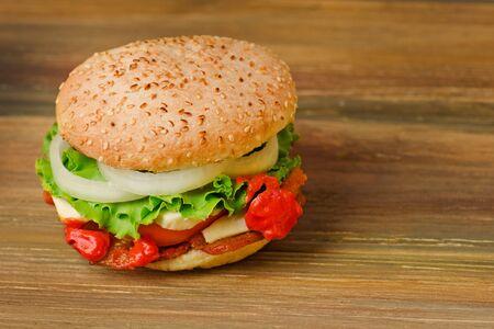 Photo pour Preparation of delicious burger in a restaurant. Delicious burger  on wood table background. Healthy chicken hamburger - image libre de droit