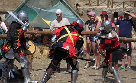 Photo for ODESSA, UKRAINE - JULY 20, 2019: Battle of the Knights with medieval weapons at the medieval performance. Knights fight on the field during the battle tournament of the festival of medieval culture - Royalty Free Image