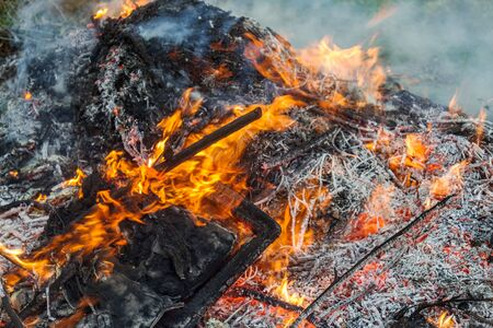 Photo for Farmer burns green waste in the concept of bonfire, bonfire outdoors, agriculture. Fallen leaves, branches and household trash burns in an autumn fire - Royalty Free Image