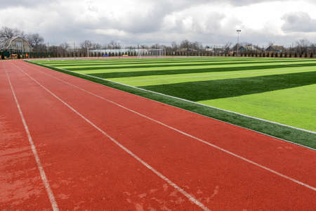 Photo pour Sports stadium with artificial turf green grass on a professional football field. Running Artificial Rubber Stadium Sports Tracks - image libre de droit