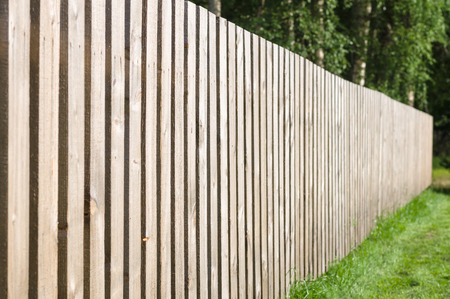 Typical wooden fence with green lawn and trees