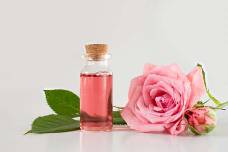 Photo for A glass jar with a pink rose. Cosmetics and perfume. Scented rose water in a glass bottle, roses. Flatly composition with a glass vessel and rose flowers on a pink background, space for text - Royalty Free Image