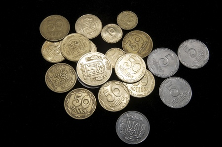 scattered small coins of Ukraine on a black background