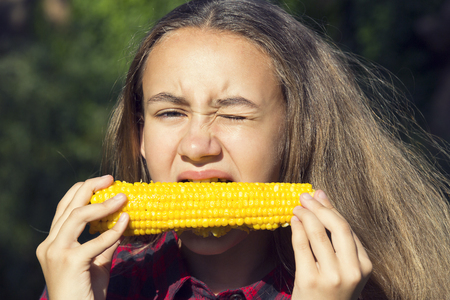 girl eating sweet corn on the nature of the day