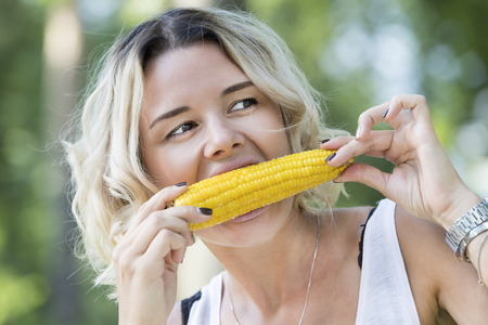 The girl is eating boiled sweet corn in the park
