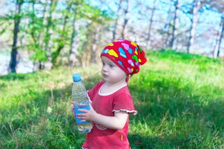 Little beautiful girl in red clothes holding a water bottle in hand