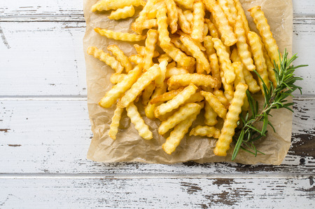 French fries over an old wooden table. Top view