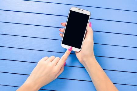 Photo pour Beautiful female hand using mobile phone over blue wooden table - image libre de droit